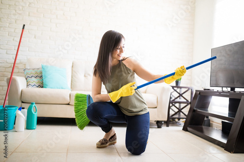 Funny housewife having fun with a broom