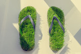 Footprint, sandals made of green artifitial grass on marble background. Save the nature, environment, ecology concept - 204930558