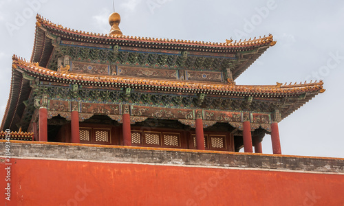 Fotobehang Peking Beijing, China - April 27, 2010: Closeup of Highly decorated upper structure of hall at Forbidden City under light blue sky. Maroon dominant with gold, brown and gold.