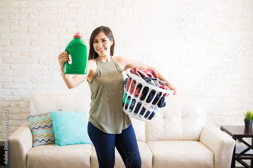 Cute housewife showing fabric softener bottle