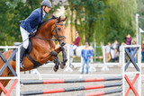 Young rider man jumping on horse over obstacle on show jumping competition - 204940133