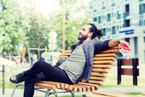 Poster lifestyle, creativity, freelance, inspiration and people concept - creative man with notebook and bag sitting on city street bench