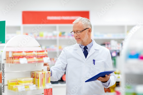 Fotobehang Apotheek medicine, healthcare and technology concept - senior apothecary with tablet pc computer at pharmacy