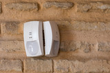 Milan, Italy - April 25, 2018: two alarm pir sensors installed on a face-facing brick wall - 204941924