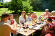 leisure, holidays and people concept - happy family having festive dinner or summer garden party - 204945179