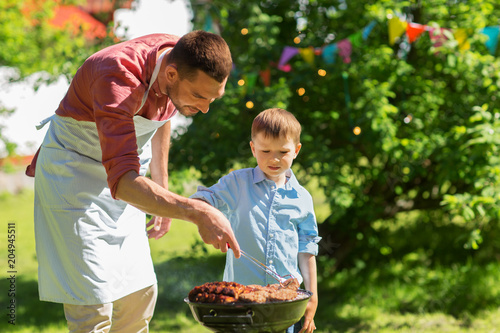 Wall mural food, people and family time concept - father and son cooking meat on barbecue grill at bbq party in summer garden