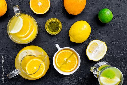 Fototapeta Refreshing summer tea with fruits. Teacup and teapot near orange, lime, lemon, grapefruit on black background top view closeup