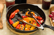 Seared peppers stuffed with cheese prepared in cast iron pan during camping trip