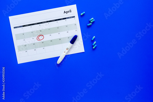 Leinwandbild Motiv Planning pregnancy. Positive pregnancy test near calendar page and pills on blue background top view copy space