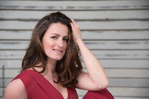 erotische junge Frau in langen roten Kleid auf altem Fabrikgelände - 204956583