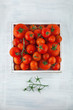 box of fresh ripe red tomatoes in different sizes on white wood kitchen table, can be used as background