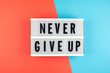 Never give up  - text on a display lightbox on blue and red bright background.
