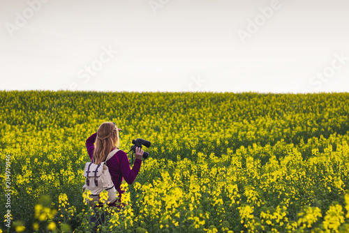 Hiking woman watching landscape with binoculars