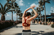 Concentrated slim young woman is raising her arms while warming up before jogging. She is standing while turning her back to camera. Summer activity concept