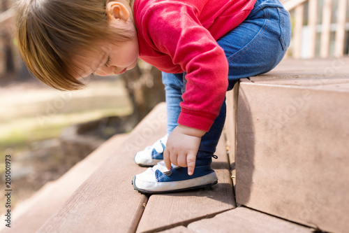 Happy toddler boy tying his sneakers outside