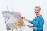 senior cheerful woman painting with palette on easel in workshop