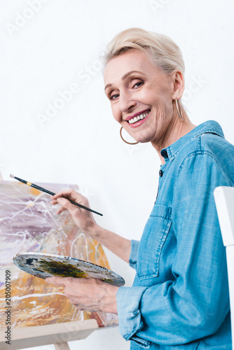senior female artist with palette and brush painting in workshop