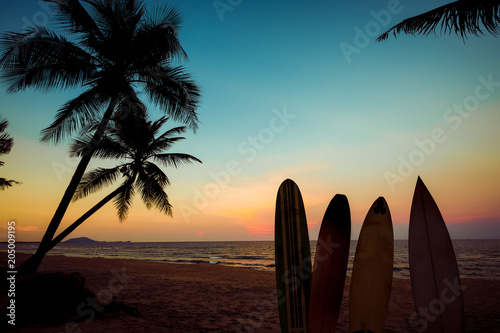 Fotobehang Strand Silhouette surfboard on tropical beach at sunset in summer. Seascape of summer beach and palm tree at sunset. Vintage color tone