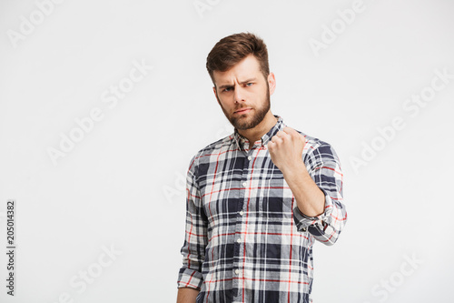 Portrait of an angry young man threatening with a fist