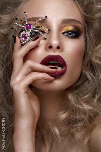 Beautiful blonde girl with curls, bright make-up and designer accessories. Beauty face. Photo taken in the studio.