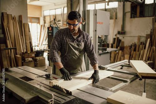 Wall mural Skilled Carpenter craftsman at work in his workshop