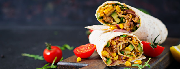 Burritos wraps with beef and vegetables on  black background. Beef burrito, mexican food. © timolina