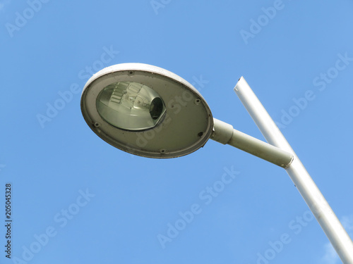 Modern street lamp post isolated on blue sky background