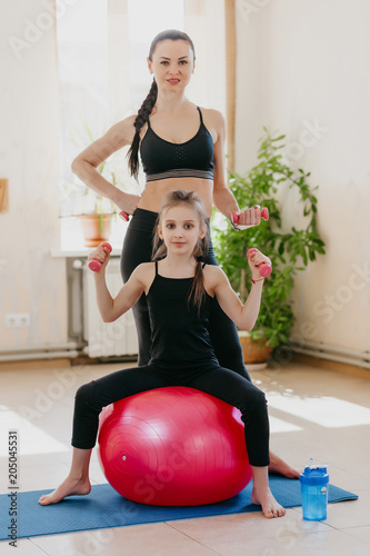 mom and daughter with dumbbells