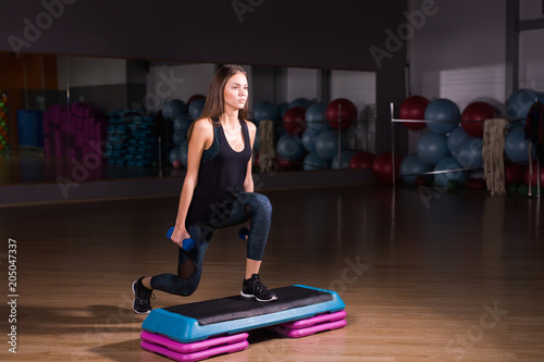 Wall mural Sporty woman practice on step platform in gym
