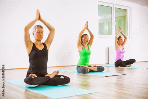 Fototapeta Three girls practicing yoga, Padmasana / Half lotus Position