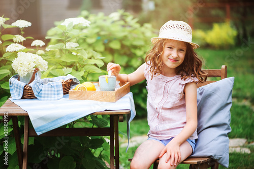 happy child girl drinking tea with lemons in summer garden in the morning.