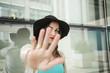 Ragazza mora con cappello nero in testa e vestito color turchese ci fa segno con la mano di STOP