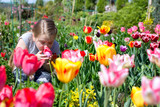 cute child smelling tulip in a beautiful garden