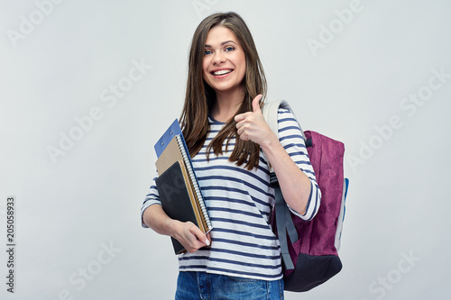Student woman showint thumb up, holding notebooks.