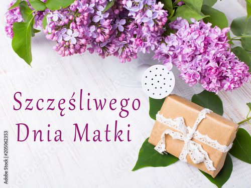 Fototapeta Dzień matki, kwiaty bzu i prezent na drewnianym tle.