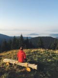 A girl in a red jacket watching the sunrise on the mountain top. Dramatic and gorgeous scene. Location Carpathian, Ukraine, Europe. Beauty world. Mobile photography