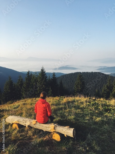 Plexiglas Zonsopgang A girl in a red jacket watching the sunrise on the mountain top. Dramatic and gorgeous scene. Location Carpathian, Ukraine, Europe. Beauty world. Mobile photography