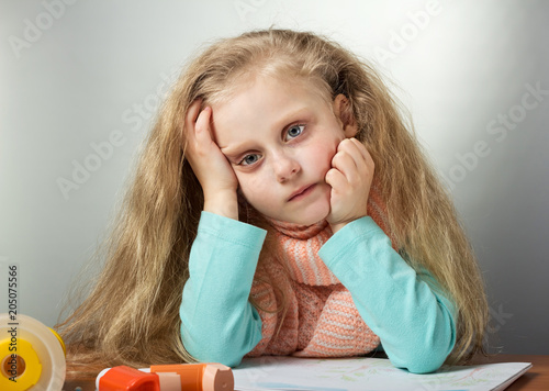 Sad sick girl in warm scarf sitting at table, near inhaler and mask