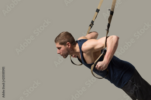 Wall mural Side view image of sportsman training muscles. Isolated on white background.