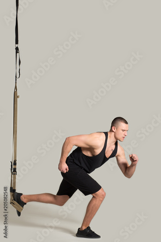 Side view image of strong sportsman doing rope workout at gym. Sport concept.
