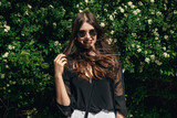 beautiful Stylish Hipster Girl with beautiful windy hair having fun at floral bushes in sunny day. Boho Woman with sunglasses in fashionable outfit, smiling and enjoying day in garden - 205083176