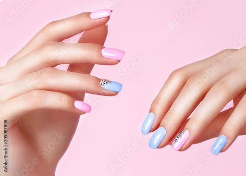 Plexiglas Manicure Beautiful pink and blue manicure with crystals on female hand. Close-up. Picture taken in the studio