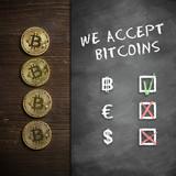 Bitcoin Münzen auf Holzuntergrund mit Wandtafel und Hinweis