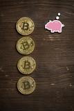 Bitcoin Münzen auf Holzuntergrund mit Sparschweinsymbol
