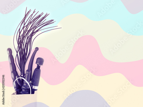 Toys for adults were bought in a sex shop and are in a paper shopping bag. Colorful wavy background. The image is suitable for advertising a sex shop (promotions, discounts, coupons) © happy_e