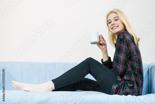 Poster Teenage woman sitting on sofa with mug