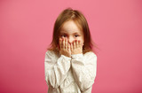 Little girl covered her mouth with hands on pink isolated background. - 205105949