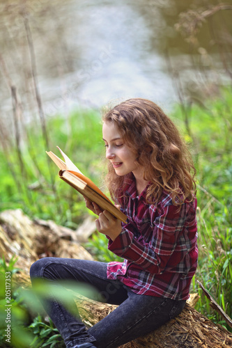 Joyful girl is reading a book in nature