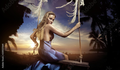 Plexiglas Konrad B. Portrait of a charming blonde sitting on a swing