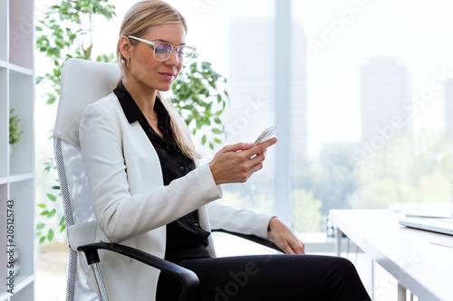 Beautiful young businesswoman using her mobile phone in the office.